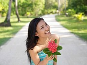 Woman holding flower, smiling