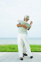 Senior couple dancing on sidewalk overlooking ocean, full length