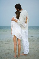 Man and teenage girl on beach, standing together, looking at view, full length, rear view