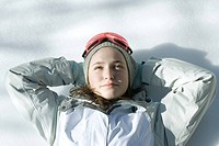 Teen girl lying on snow with hands behind head, head and shoulders