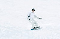 Teenage girl snowboarding on ski slope, full length
