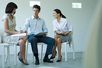 Three business associates sitting on chairs, holding documents on laps, talking