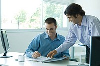 Two young businessmen looking at document together, laughing