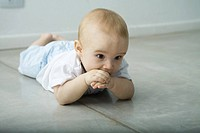 Baby lying on floor, hand in mouth