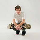 Teenage boy 14-15 squatting, holding skateboard, portrait