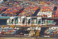 Container ship loading at dock with container yards alongside, aerial view