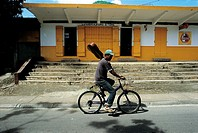Mauritius, man biking by a shop