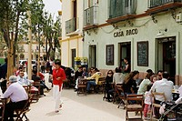 People sitting at an outdoors Tapas bar restaurant called Casa Paco in the trendy Alameda area, Seville, Spain.