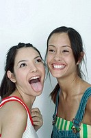 Two young female friends, one sticking tongue out, the other laughing, portrait