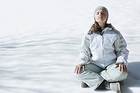 Teenage girl sitting indian style on snow with eyes closed and head back, full length
