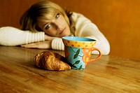 Woman sitting in front of cup and lye croissant