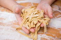 Child´s hands holding home-made ribbon pasta