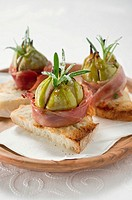 Figs wrapped in raw ham on toast
