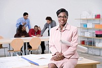Business woman sitting on desk in office, co-workers in background