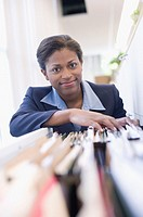 Businesswoman browsing through files in cabinet, portrait