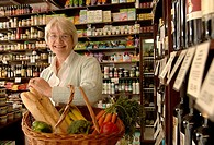 ´Senior woman with full shopping basket in delicatessen, waist up´