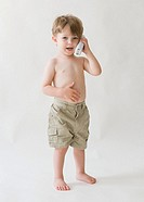 Boy 2-3 holding phone receiver to ear, white background, portrait