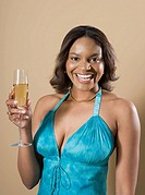 Young woman holding glass of champagne, laughing, portrait
