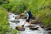 Hiker Boulder Hopping Across a River  Ukhahlamba-Drakensberg Park UNESCO World Heritage Site, KwaZulu Natal Province, South Africa