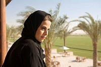 Arab Woman Standing on Balcony, Staring into Distance, Side View  Dubai, United Arab Emirates