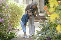 Grandmother showing granddaughter flowers