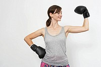 Woman wearing boxing gloves and flexing arm