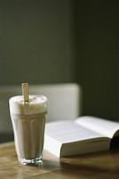 Cappuccino sitting on table beside book