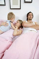 Irritated husband in bed with wife and son