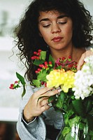 Woman adjusting flower arrangement