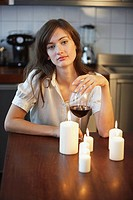 Woman sitting with wine and candles
