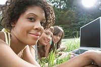 Girls using laptop computer outdoors