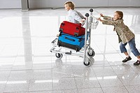 Girl pushing baggage cart in airport