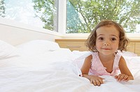 Little girl lying on bed smiling