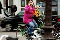 Amsterdam, a young pregnant mother on her bicycle with flowers, her toddler boy and her cell phone