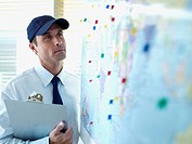 Male delivery person with cap and clipboard looking at wall map