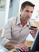 Man sitting at computer with credit card (thumbnail)