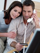 Man with credit card and computer with woman (thumbnail)