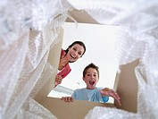 Woman and boy looking in cardboard box smiling