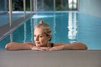 Woman leaning against an indoor pool ledge relaxed