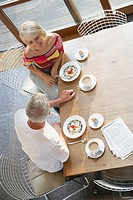Couple at table with breakfast and newspaper