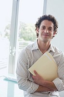 Businessman holding folder in arms in office (thumbnail)
