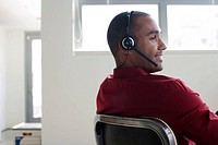 Businessman sitting in office wearing headset