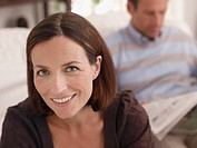 Woman smiling in living room with man in background reading