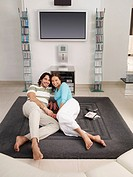 Couple lying on rug in front of television