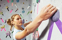 Woman grabbing purple hand hold on climbing wall
