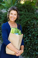Woman carrying groceries in brown bag