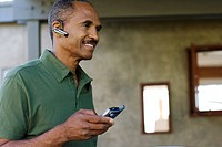man with earpiece and his mobile phone outside home