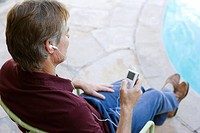 Man sitting by pool with MP3 Player