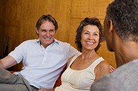 couple socializing with woman in modern home