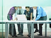 Four businesspeople in office looking at laptop